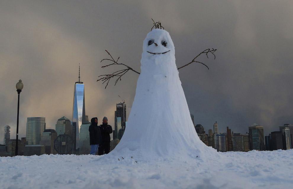 Снеговик сидит напротив нижней части Манхэттена в Нью-Йорке