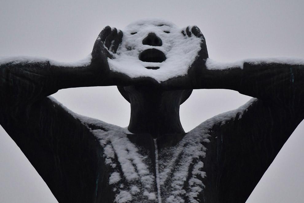 Статуя в снегу перед Бранденбургскими воротами в Берлине