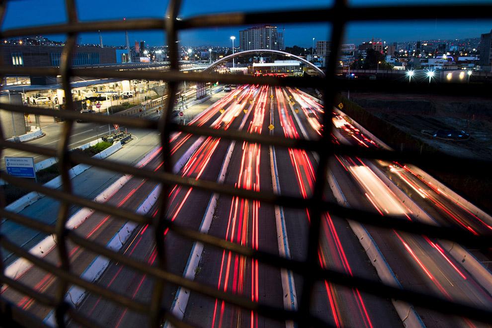 Сквозь забор видно, как машины пересекают границу с Мексикой
