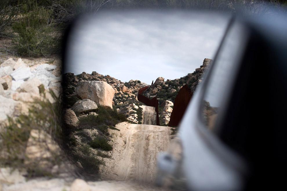 Граница США и Мексики в отражении зеркала в автомобиле