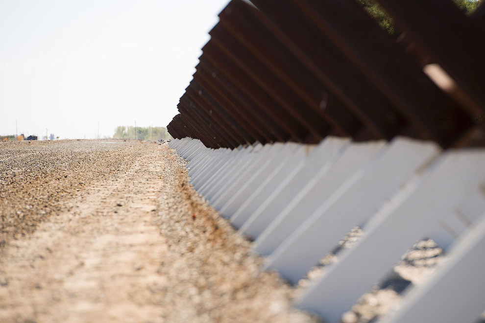 Пограничный забор вдоль реки Колорадо в Юма, штат Аризона