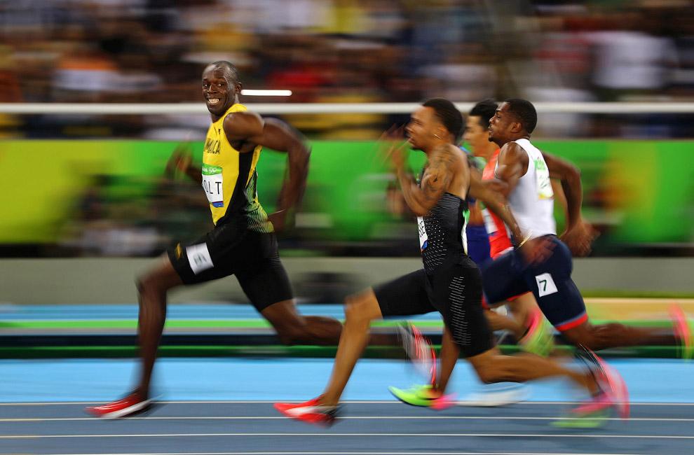 Усэйн Болт из Ямайки с улыбкой обходит своих конкурентов на 100-метровке
