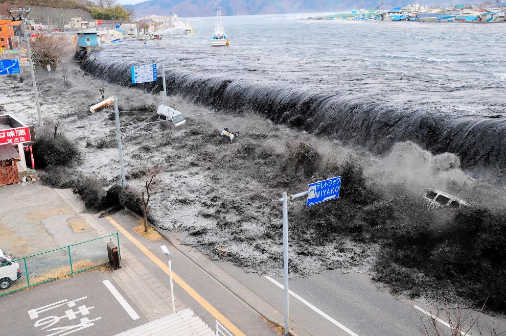 Волна переливается на улицу в Мияко в префектуре Иватэ