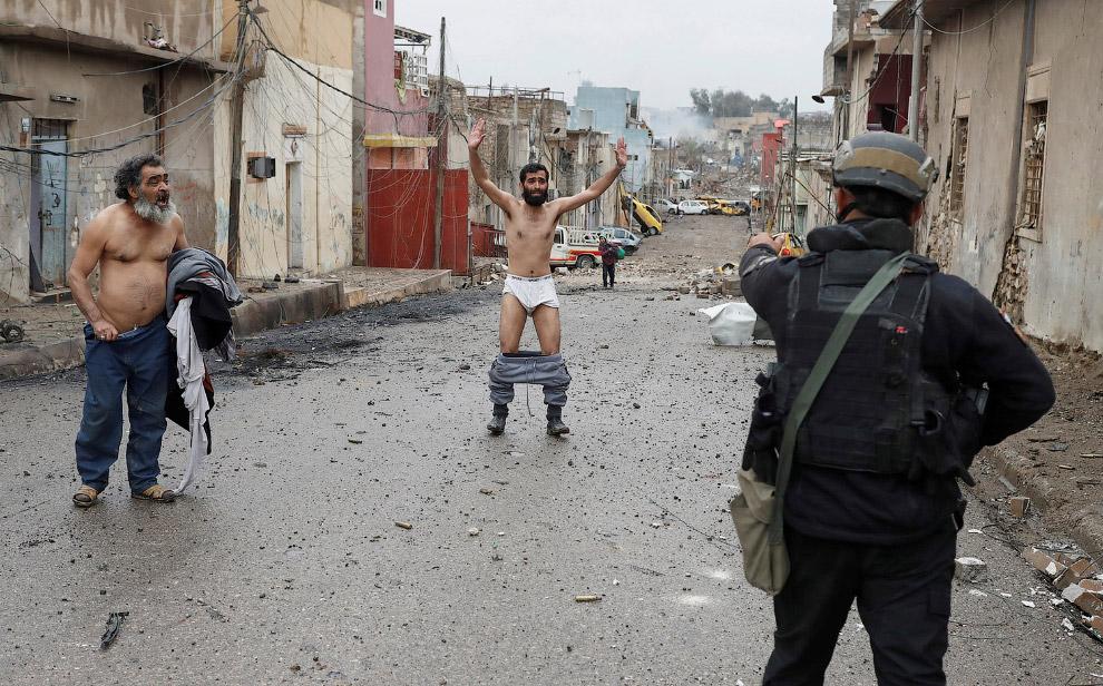 Иракский солдат таким образом проверяет людей на наличие взрывных поясов, которые идут с территории