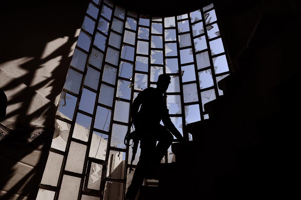 Иракский полицейский поднимается по лестнице полуразваленного здания