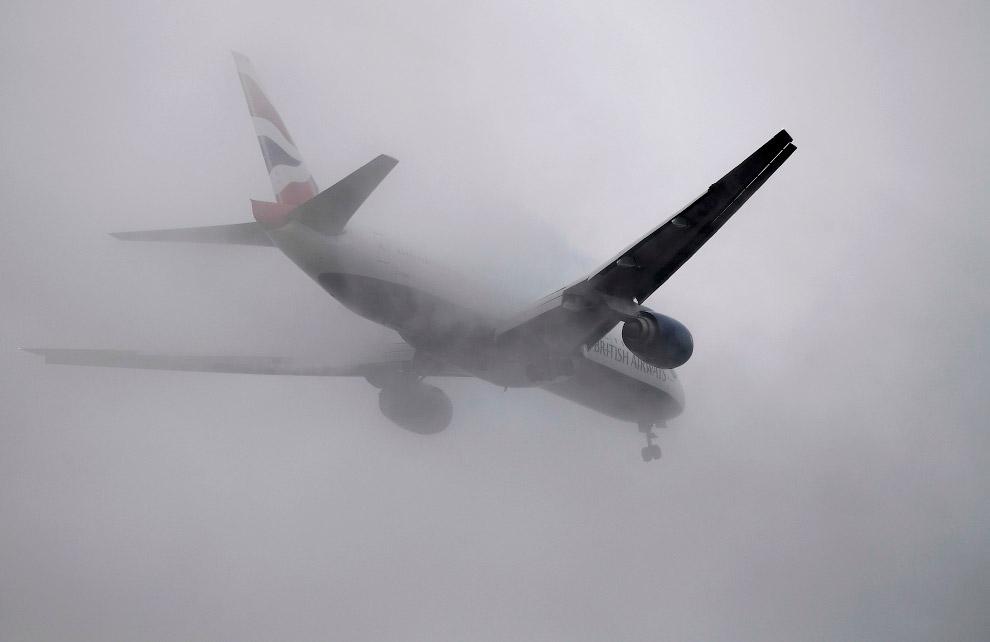 Самолет на посадке против тумана в аэропорту Хитроу в Лондоне