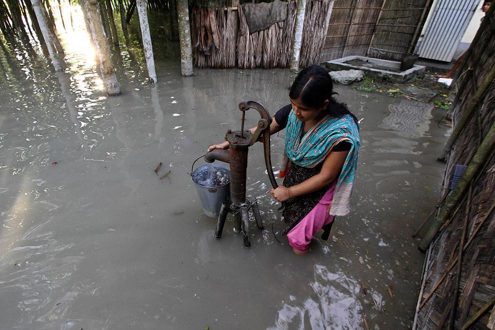 Набор воды сомнительного качества с помощью ручного насоса в индийском штате Ассам