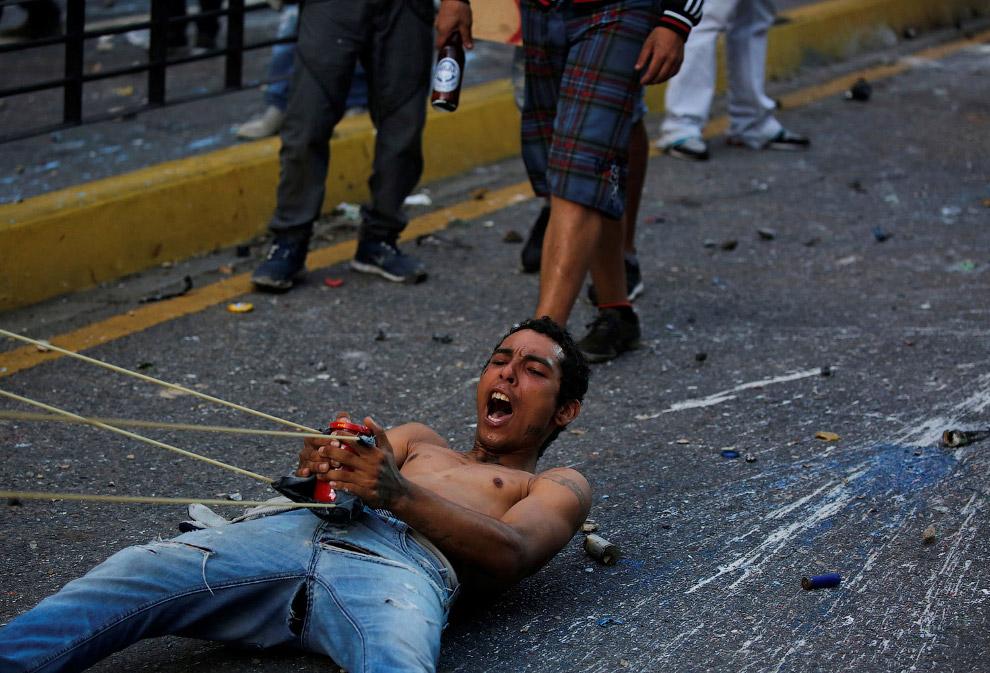Сторонники оппозиции используют гигантскую рогатку во время столкновений с силами безопасности на митинге в Каракасе