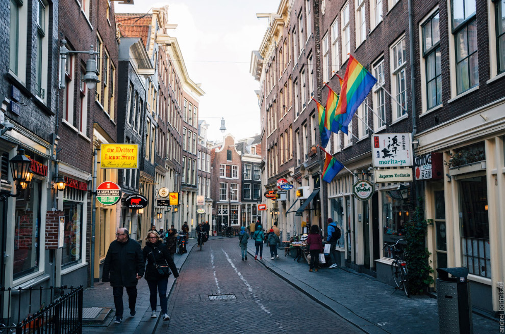 Tourist walking along a narrow street of the historical town part of Amsterdam.
