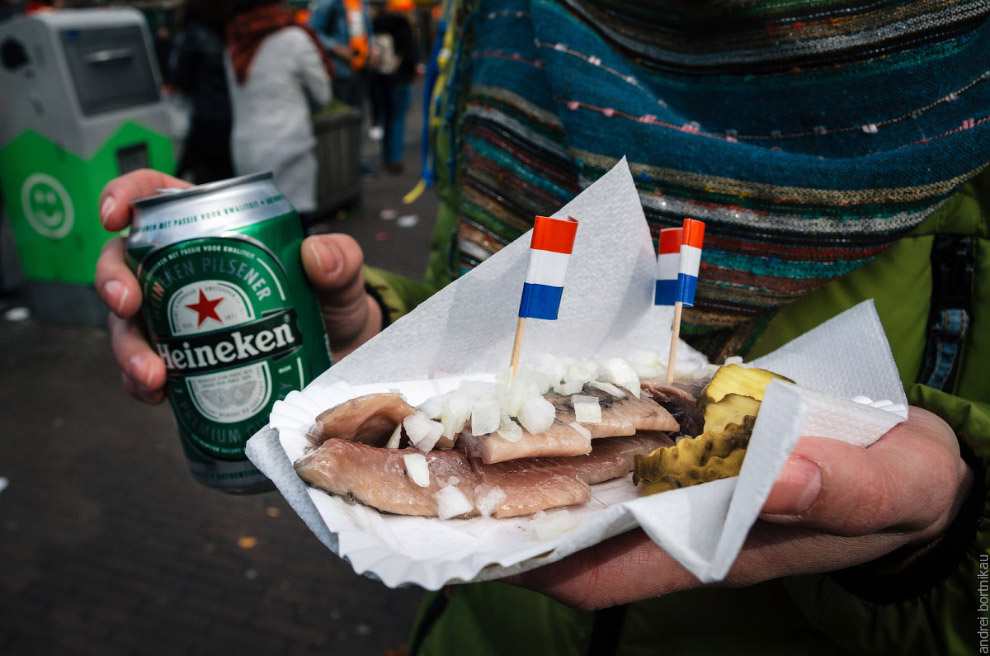 Hands hold a beer Heineken and a Dutch delicacy of herring with gherkins and onions.