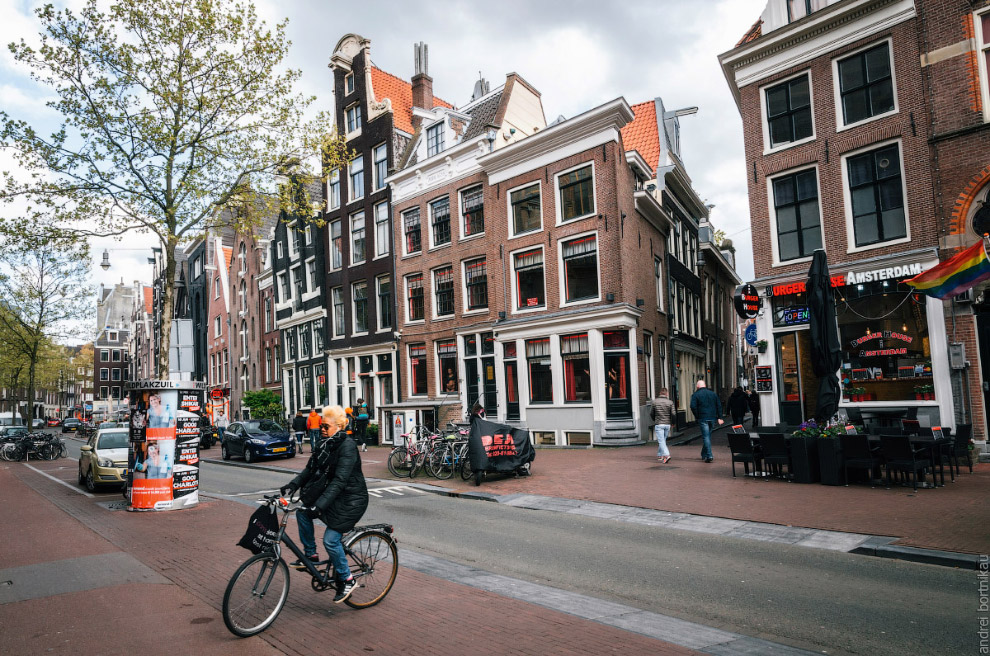 Adult woman rides a bicycle in red light district of Amsterdam, Netherlands
