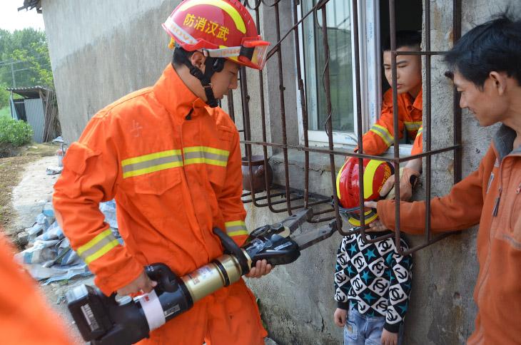 Спасатели в Ухане вытаскивают застрявшего мальчика, провинция Хубэй, Китай