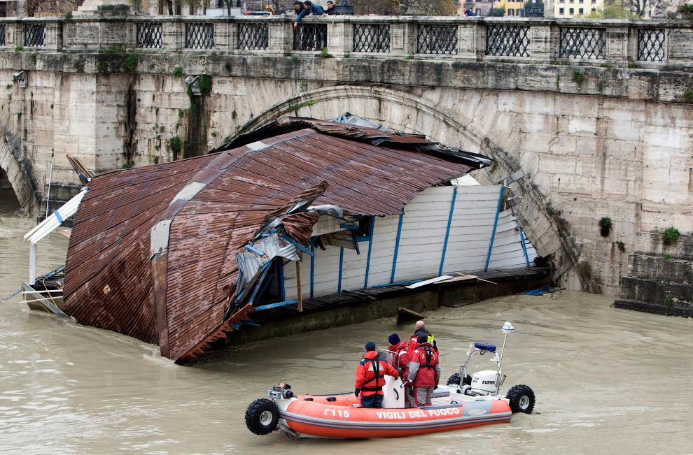 Лодка застряла в арке моста Сант-Анджело на реке Тибр в центре Рима
