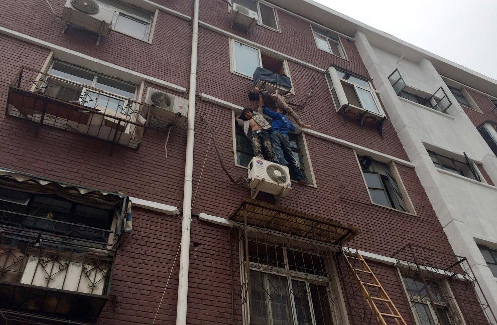 Двое поддерживают женщину в ожидании спасателей, которая выпала из окна своей квартиры, по застряла в крепеже кондиционера