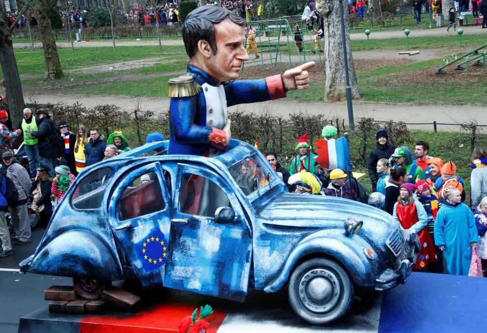 Президент Франции Эммануэль Макрон в виде Наполеона в полуразвалившемся Ситроене 2CV с флагом ЕС на двери