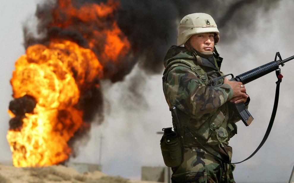 Американский солдат стоит рядом с горящей нефтяной скважиной в Румайле