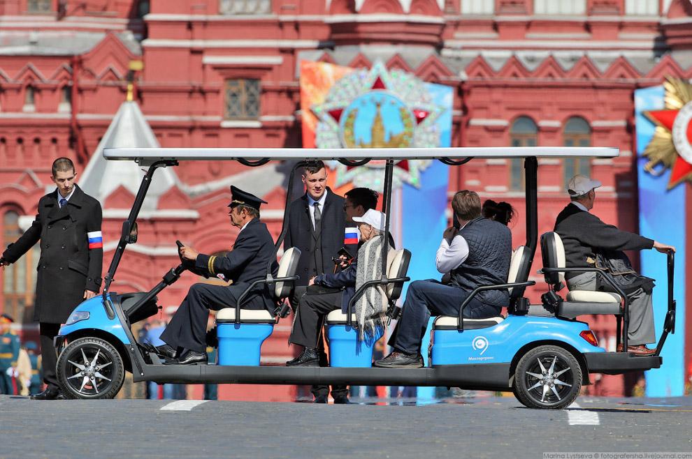 Ветеранов подвозят на электромобилях.