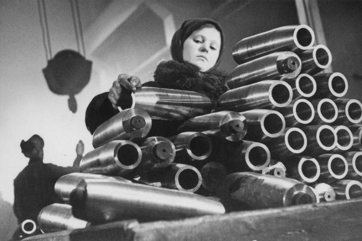 В цехе завода. Девочка укладывает болванки снарядов