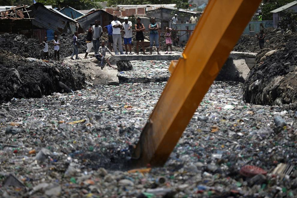 Экскаватор пытается очистить реку от пластика под Порт-о-Пренс, Гаити