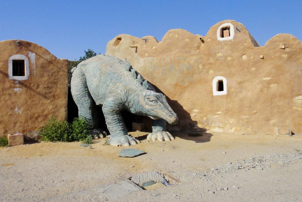 Динозавр на страже в старом парке в Тунисе