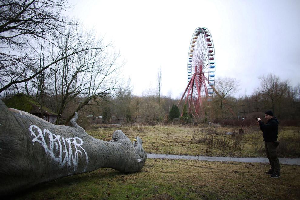 Стекловолоконный динозавр в заброшенном парке в Берлине