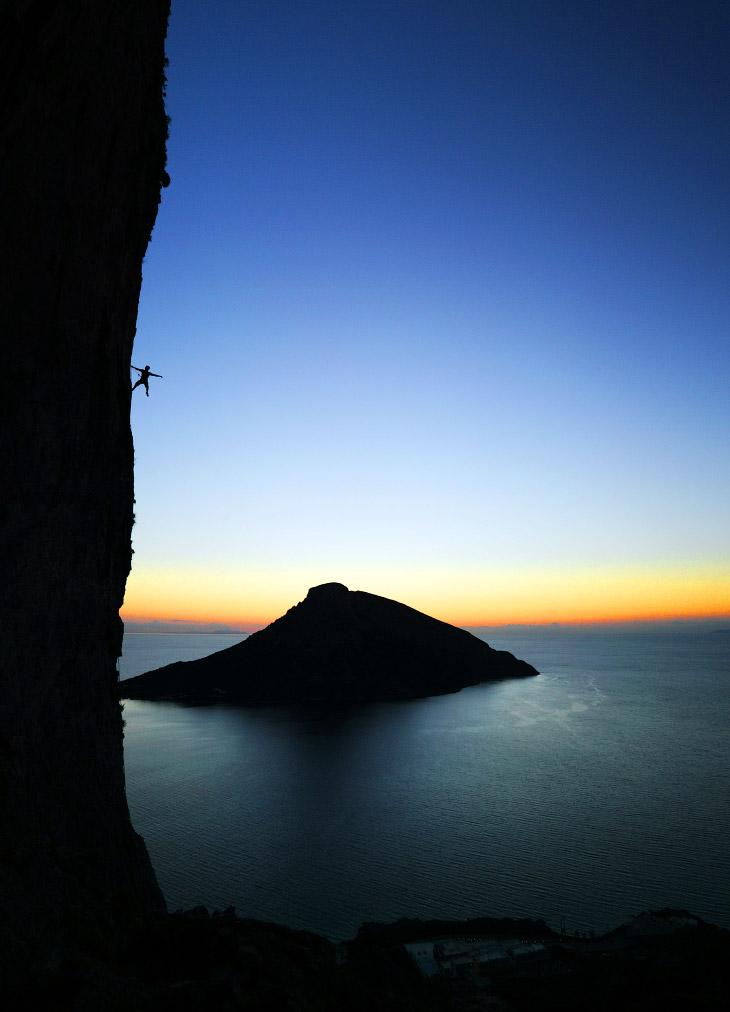 Альпинист на утесе на острове Калимнос, Греция
