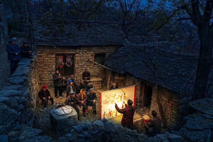 Вистава для місцевих жителів у дворі кам'яного будинку в Китаї