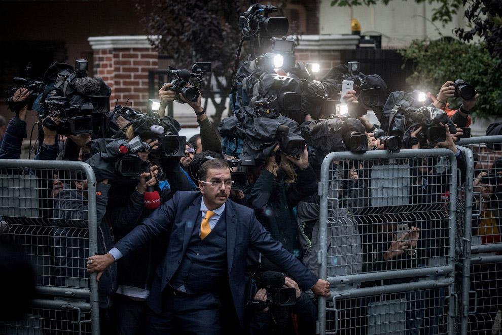 Охранник сдерживает прессу у консульства Саудовской Аравии в Стамбуле