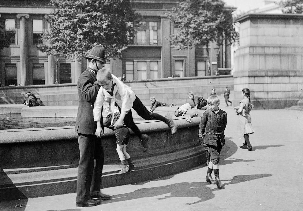 Полицейский задерживает мальчишку на Трафальгарской площади в Лондоне