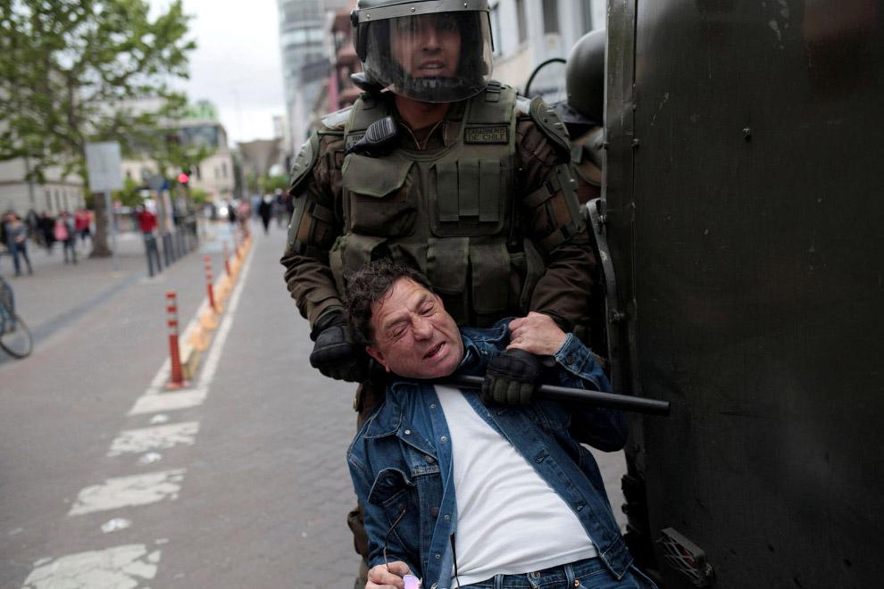 Сотрудник полиции задерживает протестующего в Консепсьоне