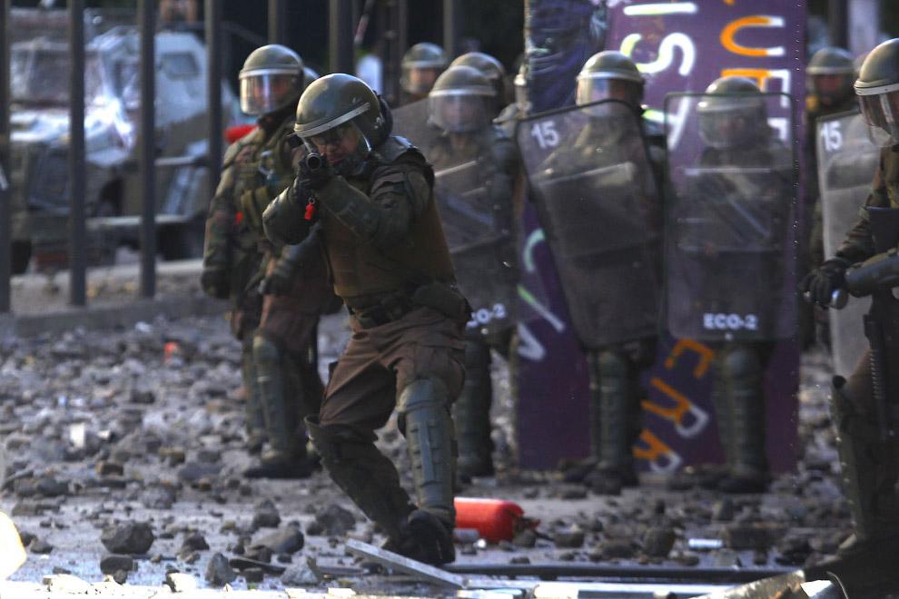 Сотрудник ОМОНа стреляет по демонстрантам