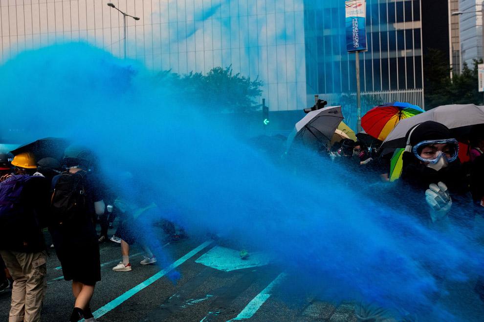 Полицейские разгоняют протестующих какой-то синей жидкостью
