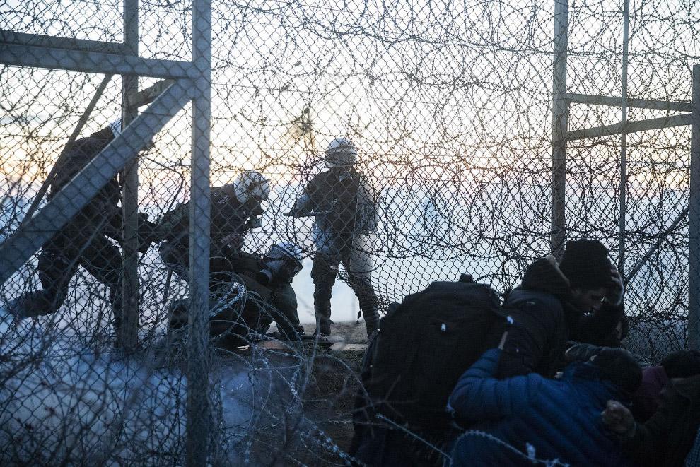 Греческие пограничники против мигрантов, пытающихся пересечь границу через отверстия в заборе