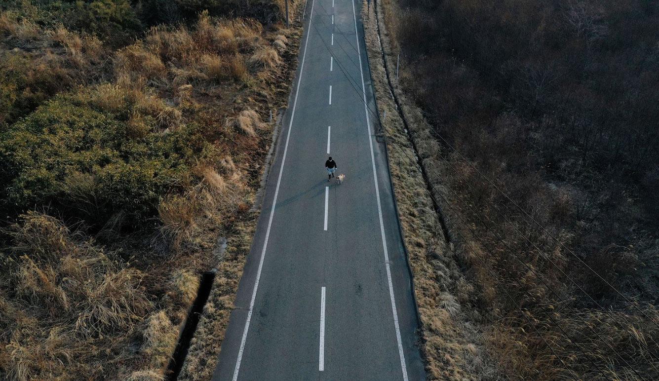 Одинокий житель на дороге в префектура Фукусима