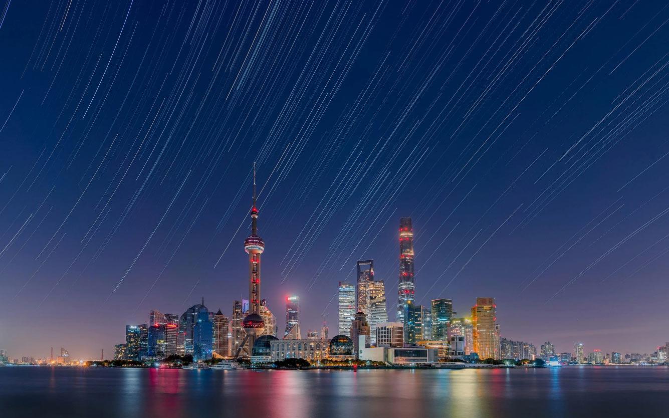 Звездные треки над городом Луцзяцзуй в районе Пудун, Китай