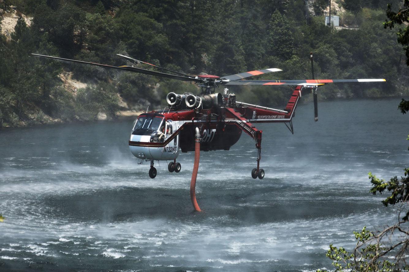Пожарный вертолет набирает воду