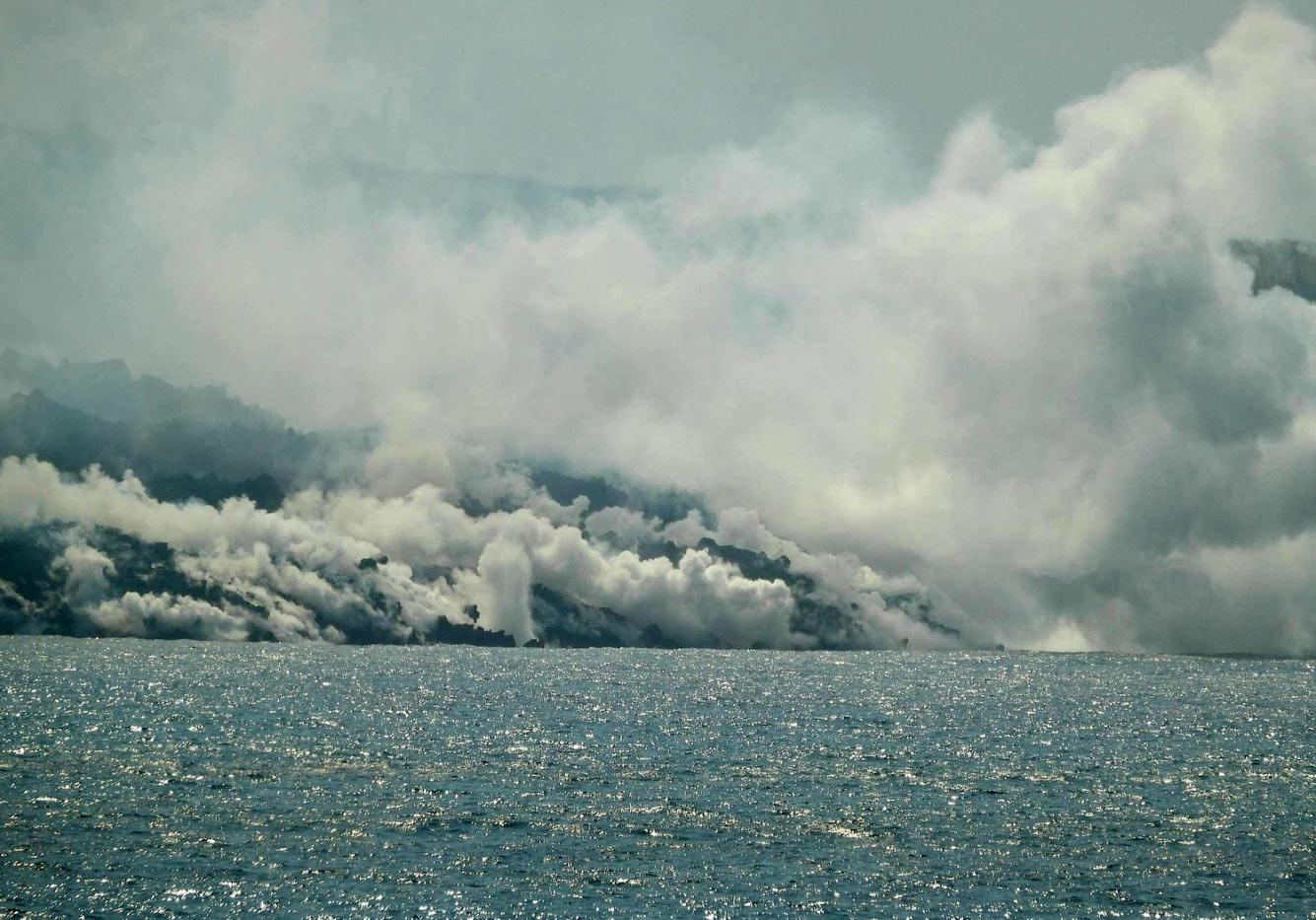Лава течет в Атлантический океан на пляже Лос-Гиррес в Тасакорте