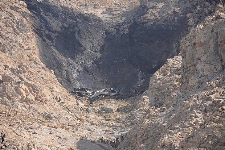 Афганские спасатели  перевозят обугленные останки пяти погибших в авиакатастрофе близ Кабула, Афганистан, в среду, 13 октября 2010