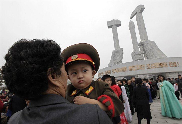 Женщина несет мальчика, одетого форму северокорейской армии