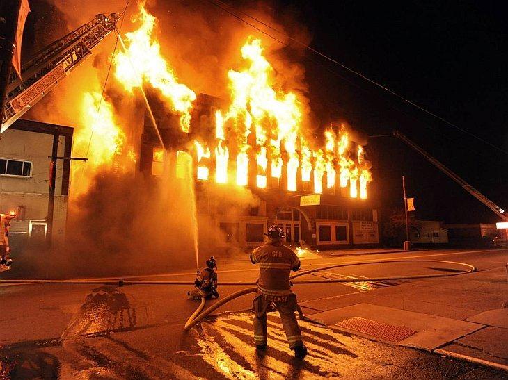 Два пожарных борются с пожаром на блошином рыноке Гарвер в Страсбурге, штат Огайо