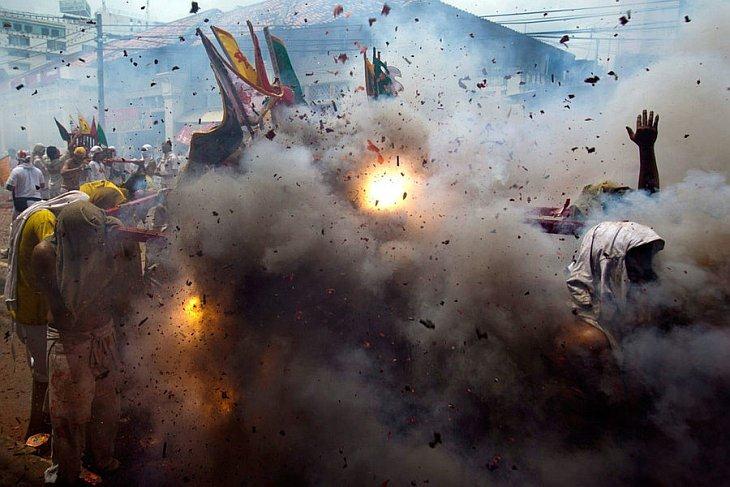 Подвижники китайской святыни Жуй Туй несут китайского бога на паланкине в то время как рядом взрываются фейерверки