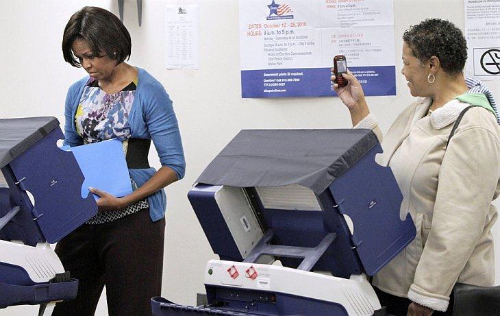 Amanda Deisch фотографирует первую леди США Мишель Обама, когда она бросает бюллетень во время досрочного голосования в Чикаго,