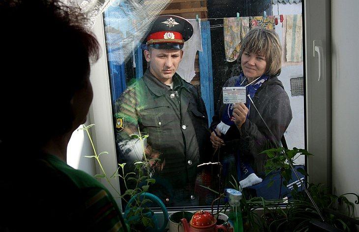 Переписчик, сопровождаемая милиционером, показывает свое удостоверение личности через окно в Кемерово, Россия, четверг, 14 октября