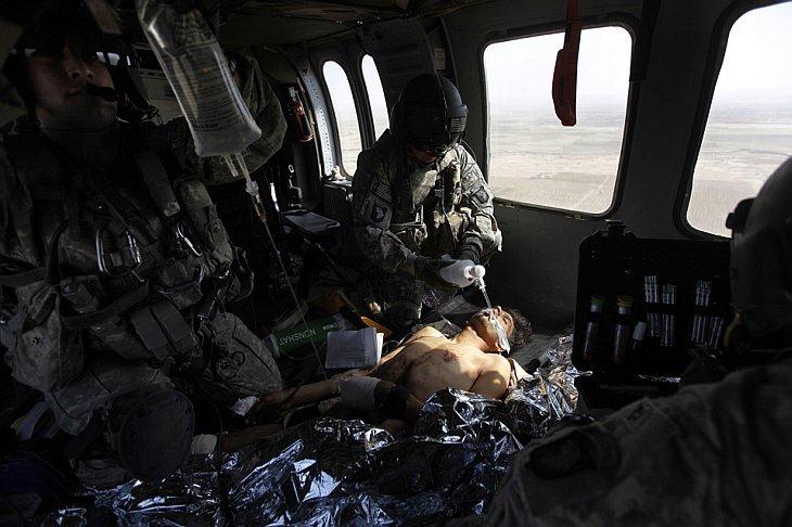 Армия медиков из США на борту вертолета в провинции Кандагар, Афганистан, четверг, 14 октября осматривают солдата Афганской национальной армии, которому оторвало ногу от придорожной бомбы