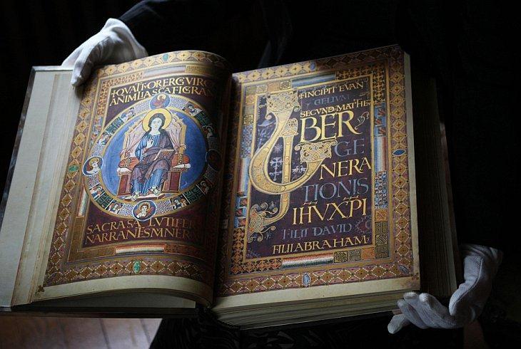 Куратор Королевской коллекции Deborah Clarke держит в перчатках Евангелие, которое стало доступно для показа во вторник, 12 октября 2010