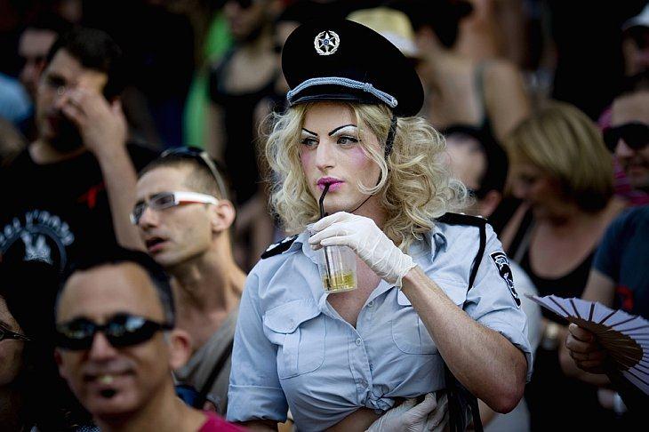 Человек, одетый как женщина-полицейский стоит в толпе во время Wigstock-2010 в Тель-Авиве
