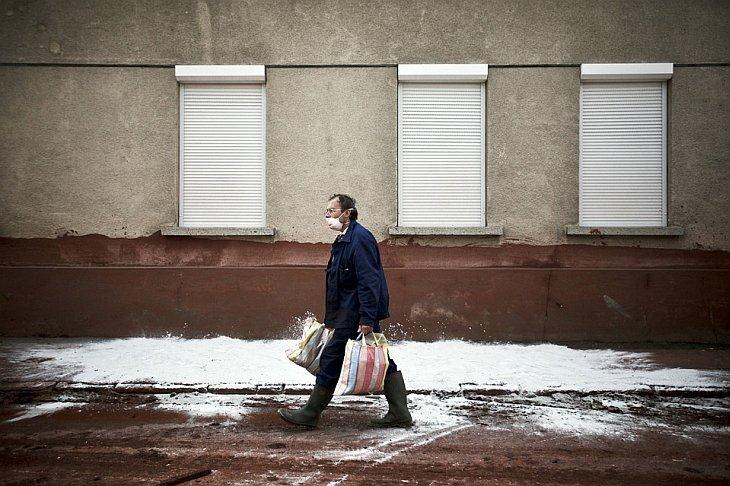 Человек, одетый в защитную маску, идет домой в среду в городе Дечевер, Венгрия, 13 октября 2010