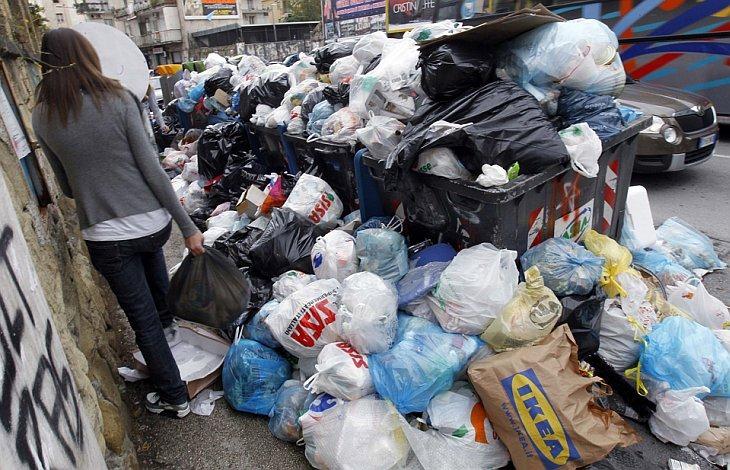 Девушка идет по тротуару мимо мусора в Неаполе