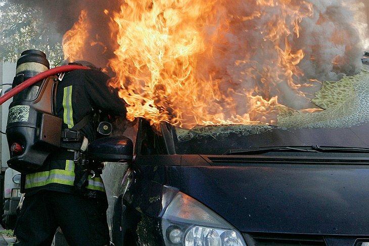 Пожарный пытается потушить горящий автомобиль во время беспорядков в Нантер, в пригороде Парижа