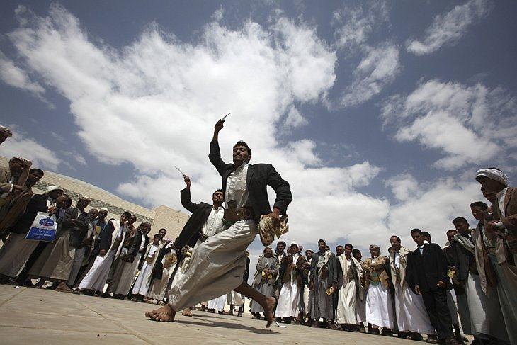 Мужчины исполняют традиционные танцы во время массовой свадебной церемонии
